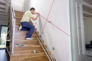 Mann bringt Geländer an mit Baulaser
